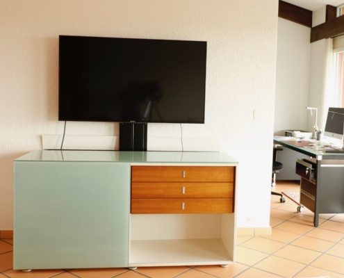 TV mit E-Lift hinter Sideboard